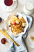 Pancakes with butter, fruit and maple syrup