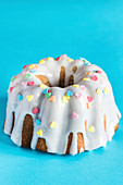 Bundt cake with icing and heart-shaped sugar sprinkles