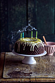 Chocolate Bundt cake with a pistachio glaze and four blown-out candles