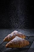 Zwei Croissant mit Puderzucker auf Abkühlgitter
