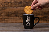 Person holding cookie over black mug with hot coffee