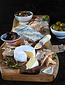 A cheese platter with nuts, olives and pomegranate jelly