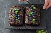 Pastry chef decorates brownie cake with blueberries and mint leaves