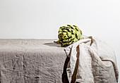 Artischocke auf Tisch mit Leinentischdecke