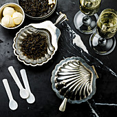 Black caviar in silver bowl and Champagne on black marble background
