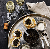 Black Caviar, Mini Pancakes and Sour Cream Holiday Party Appetizer on dark marble background