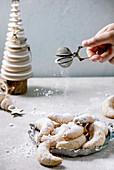 Homemade traditional Christmas shortcrust cookies vanilla crescents with icing sugar sprinkling from sieve