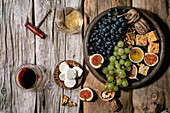 Wine appetizers with different grapes, figs, walnuts, bread, honey and goat cheese