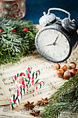 Candy canes, hazelnuts and alarm clock on music sheet
