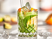 A green smoothie made with oranges and ice cubes