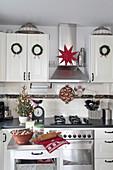 Weihnachtlich dekorierte Landhausküche mit Kränzen und Stern