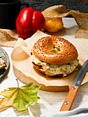 A bagel filled with minced meat, red pepper and cheese