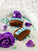 Mini chocolate cakes decorated with blue buttercream, sugar pearls and purple flowers