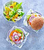 Tuna burger in a sesame seed bun with a fennel and orange salad