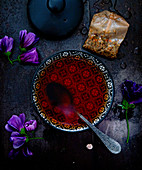 Brewed purple mallow tea in a bowl next to a teabag