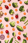 Tomatoes, broccoli, carrots, ginger and onion on pink background