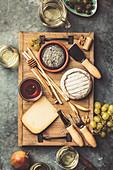 Käseplatte mit Trauben, Nüssen, Oliven, Honig und Schaumwein