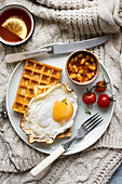 Breakfast with fried egg, baked beans and waffles