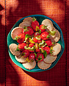 Strawberry and tomato salad with olive oil and crackers