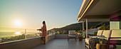 Woman with white wine enjoying sunset ocean view