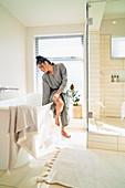 Woman in bathrobe preparing soaking tub for bath