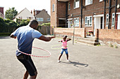 Father and daughter playing with plastic hoops