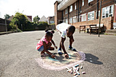 Brother and sister drawing rainbow on pavement