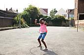Playful girl spinning in plastic hoop in neighbourhood