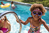 Portrait cute girl in swimming goggles at swimming pool
