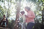 Mother helping daughter balance on fallen log in woods