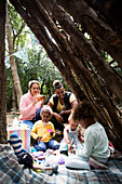 Family enjoying tea party in fort outdoors