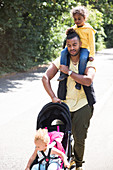 Father carrying and pushing daughter in stroller