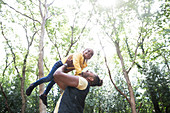 Playful father lifting daughter below trees in park