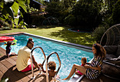 Happy family relaxing at sunny summer poolside patio