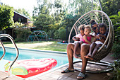 Father and daughters cuddling in poolside swing chair