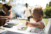 Toddler girl eating in high chair on summer patio