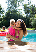 Happy mother holding daughter in summer swimming pool