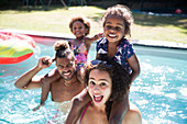 Portrait playful family in sunny summer swimming pool