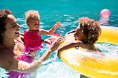 Mother and daughters playing in summer swimming pool