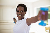 Confident senior woman exercising with dumbbells