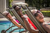 Portrait senior women friends sunbathing in lounge chairs