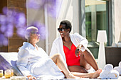 Senior women friends relaxing on summer hotel patio