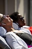 Senior woman with earbud headphones sunbathing on patio