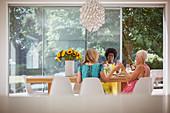 Senior women friends enjoying luncheon with wine