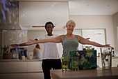 Senior women friends exercising online at laptop