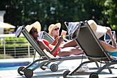 Senior women friends sunbathing at summer poolside