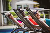 Portrait senior women friends sunbathing at poolside