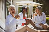 Portrait senior women friends relaxing on hotel patio