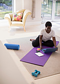 Mature woman working at laptop on yoga mat at home