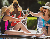 Senior women friends drinking champagne on summer patio